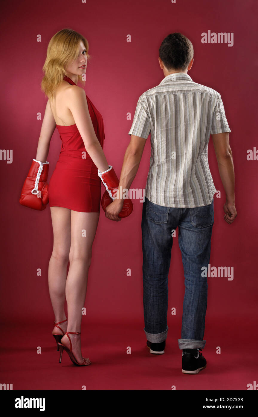 Attractive elegant woman with boxing gloves and a young man walking hand in hand - Stock Image