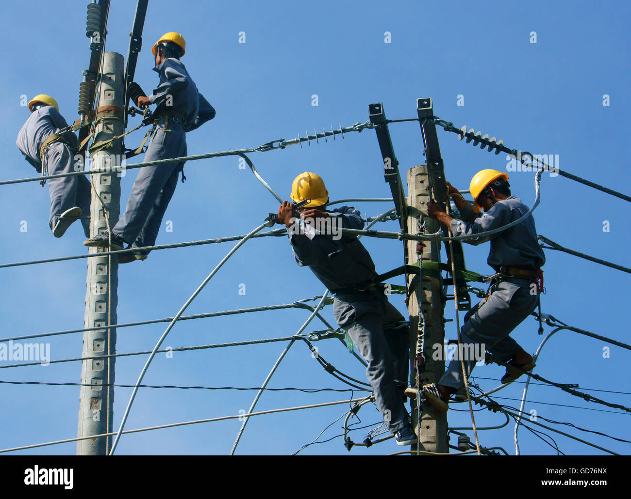 Asian Electrician Climb High In Pole To Work Lineman With