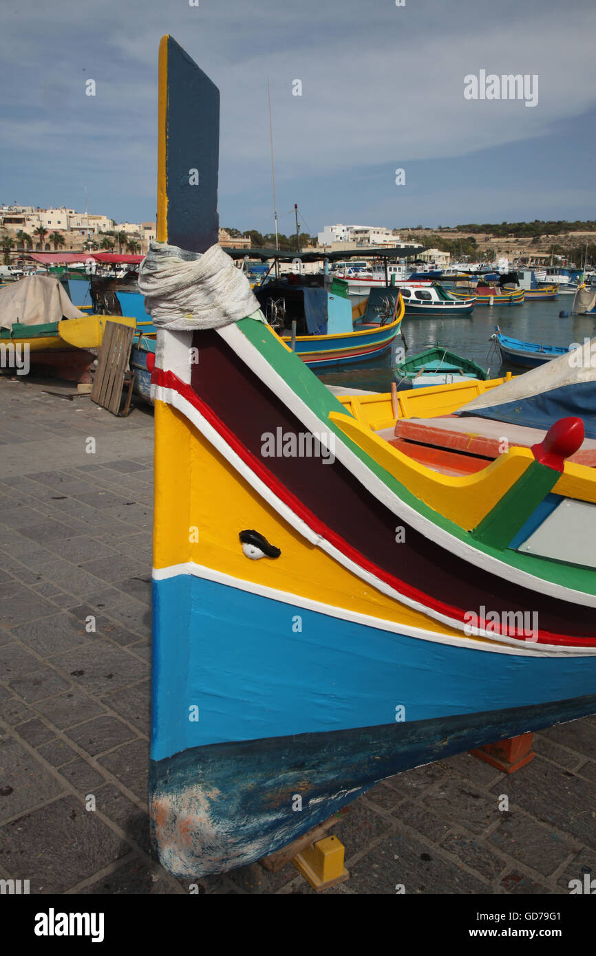 A Maltese traditional fishing boat, the Luzzu being repainted in the bright primary colours popular in Malta - Stock Image