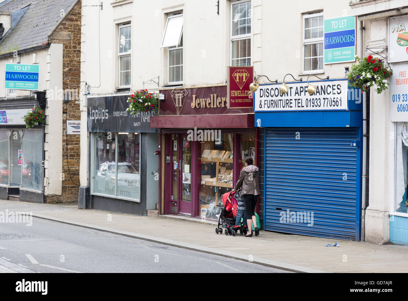 A woman pushing a child in a buggy past shops in Wellingborough Northamptonshire UK - Stock Image