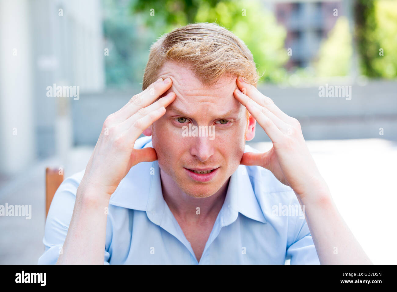 Closeup portrait, stressed young business man in blue shirt, hands on head with bad headache, isolated background - Stock Image