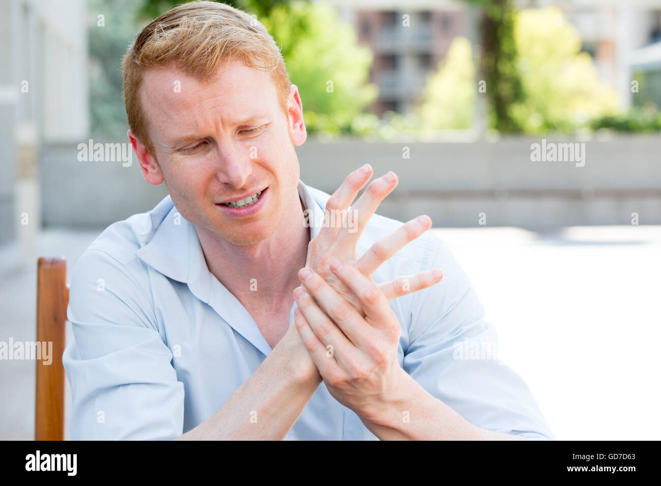 Closeup portrait, young man having acute bad joint pain in his hands, writer's cramp, massaging them, sitting - Stock Image