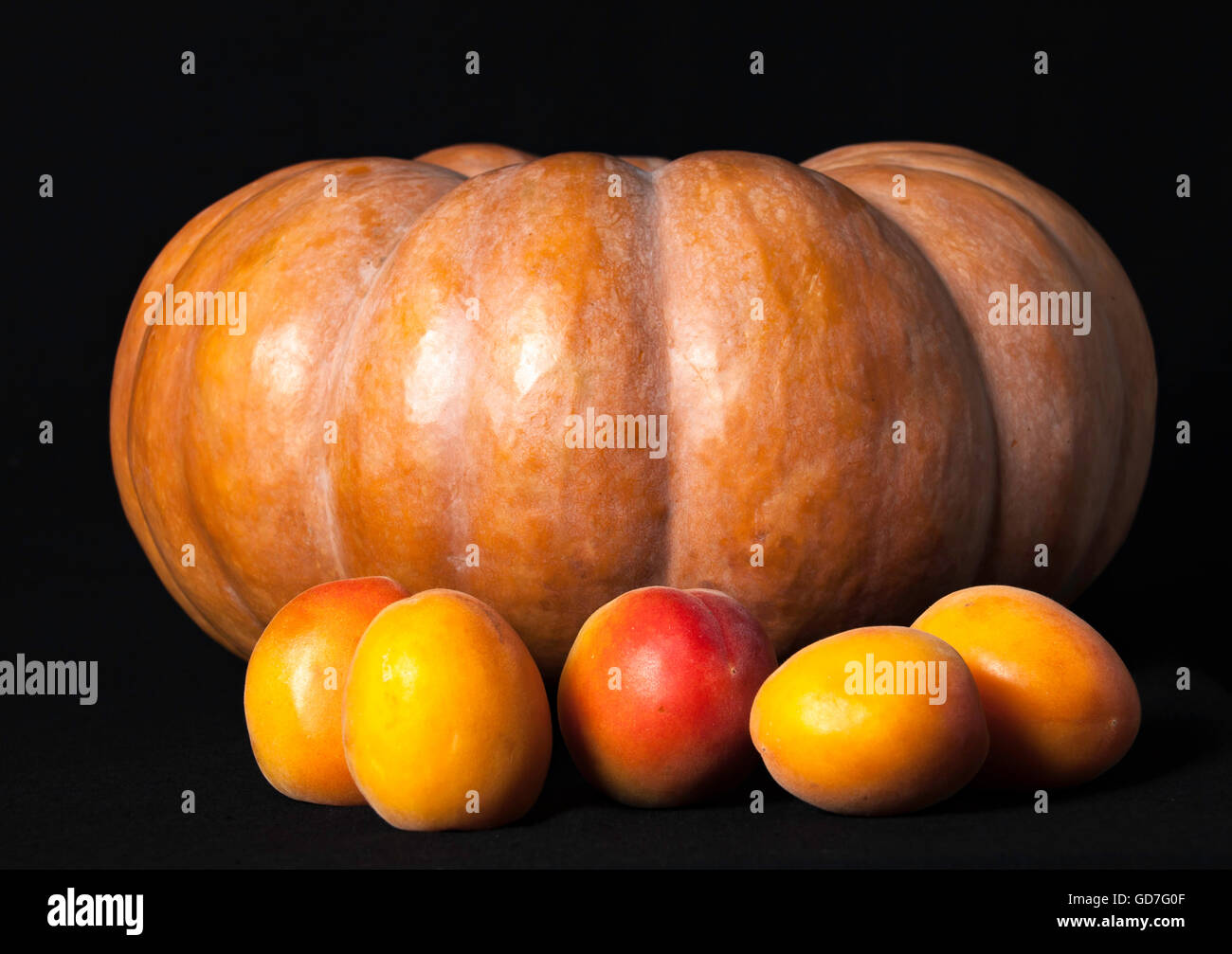 Pumpkin and 5 Peaches photographed on black backdrop in Studio - Stock Image