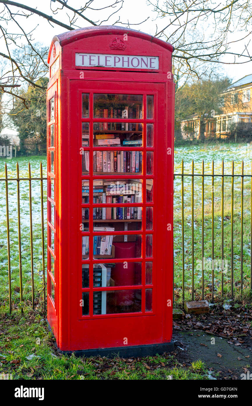 Red telephone box being used as a library in a village in England. - Stock Image