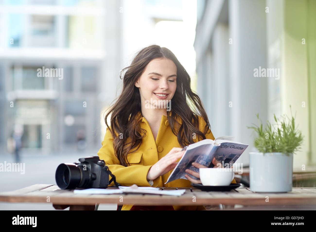 happy woman with guide drinking cocoa at city cafe - Stock Image