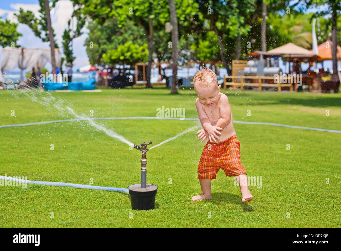 Happy baby boy playing with sprinkler spray and splashing with fun under water drops on beach club green grass lawn. - Stock Image