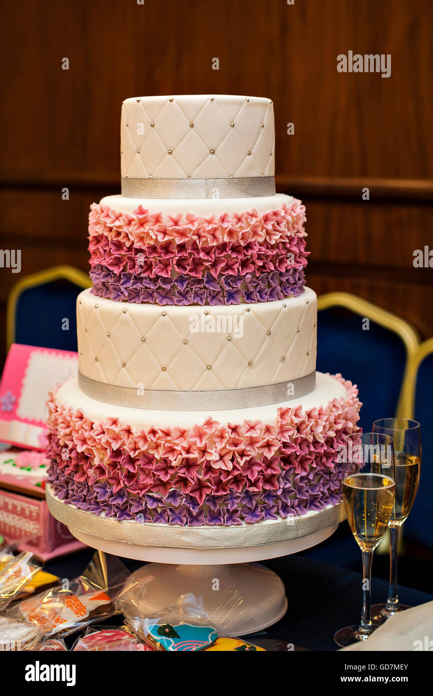 White Multi Level Wedding Cake With Pink Flower Decorations Stock
