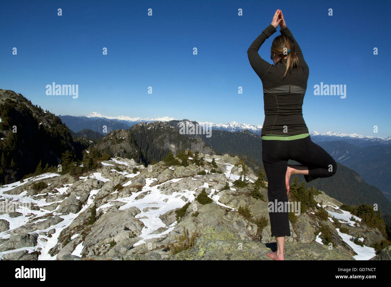 Middle-Aged Caucasian Woman Holding Hatha Yoga Tree Pose on Winter Snowcap Sunshine BC Mountain Peaks with Blue - Stock Image