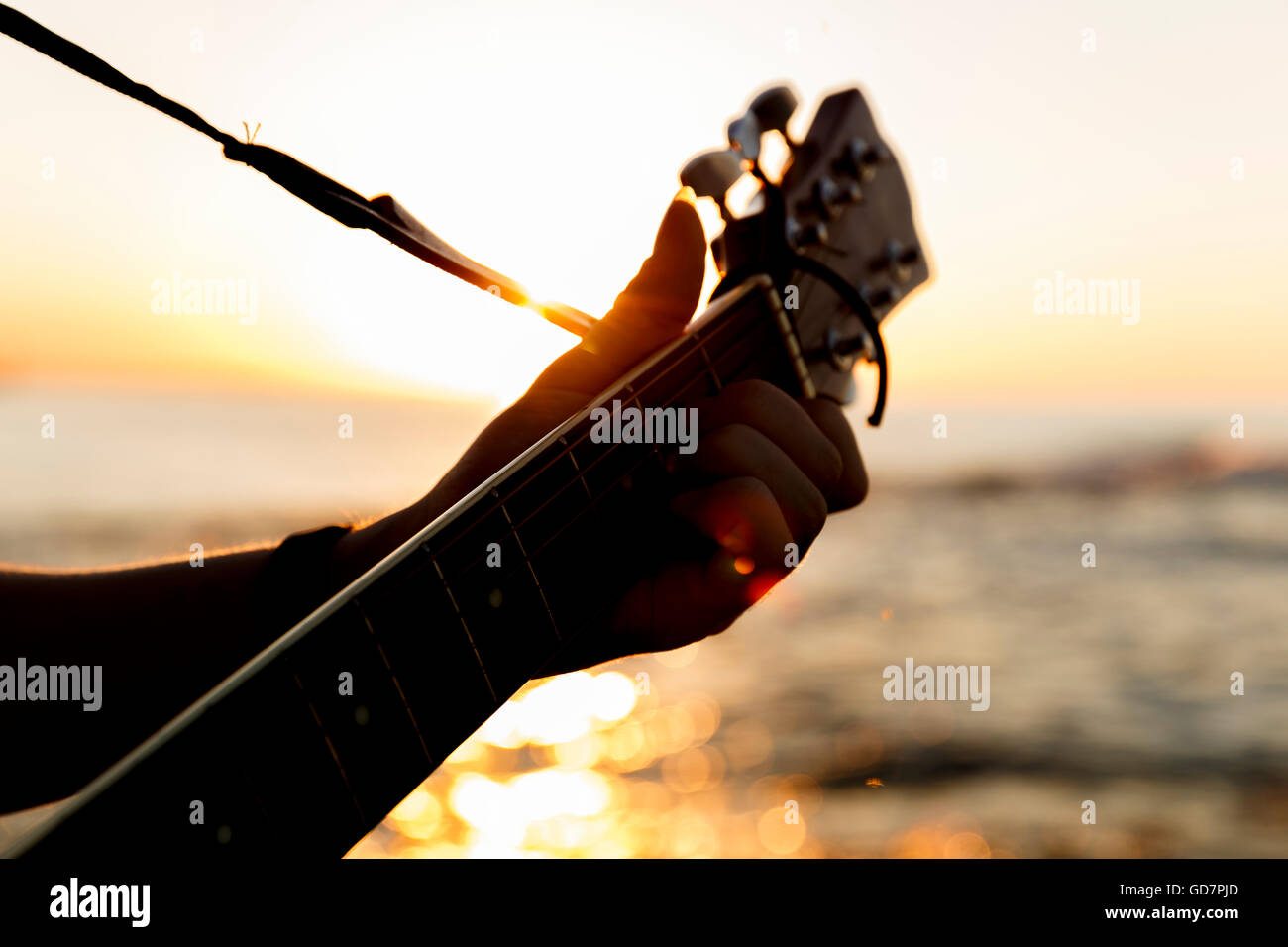 Young guy playing a guitar at sunset(Soft Focus) - Stock Image
