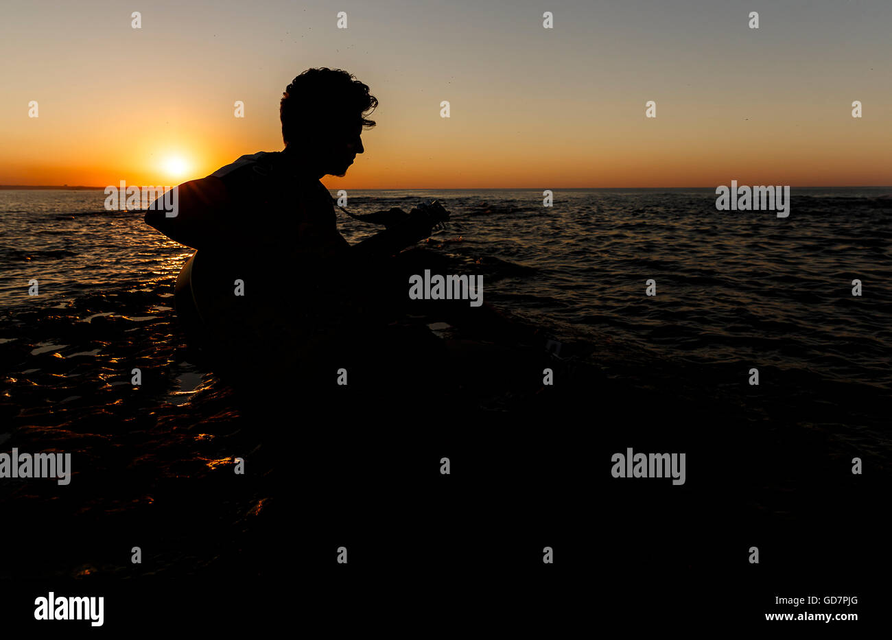 Young guy playing a guitar at sunset - Stock Image