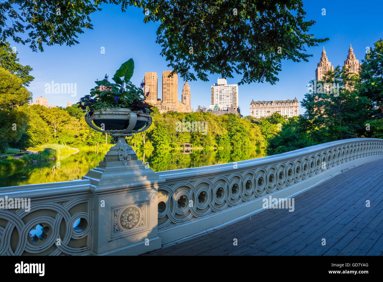 Bow Bridge in Central Park, New York City, with Upper West Side residential buildings visible in the distance - Stock Image