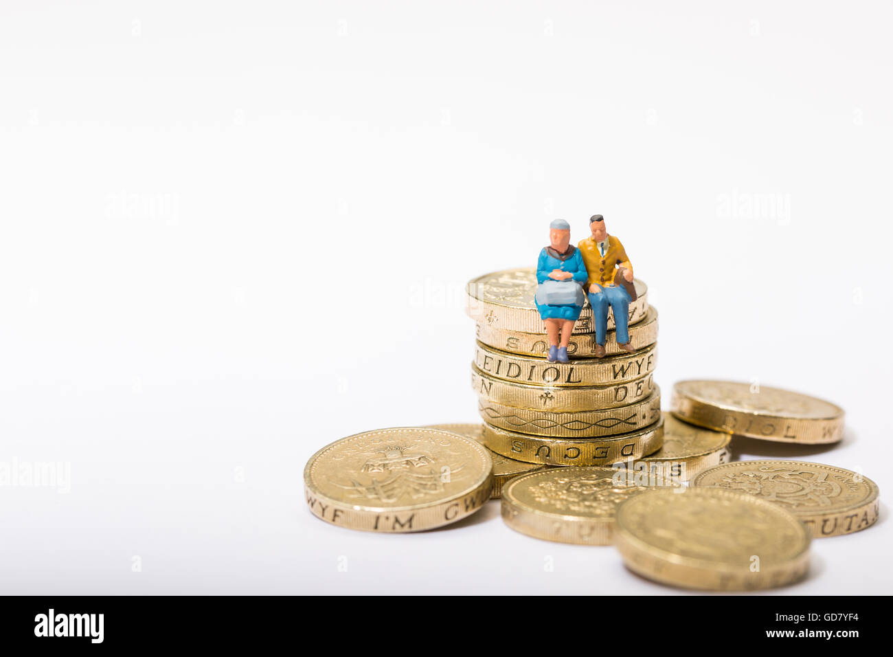 Concept image of two pensioners sat on a pile of pound coins - Stock Image