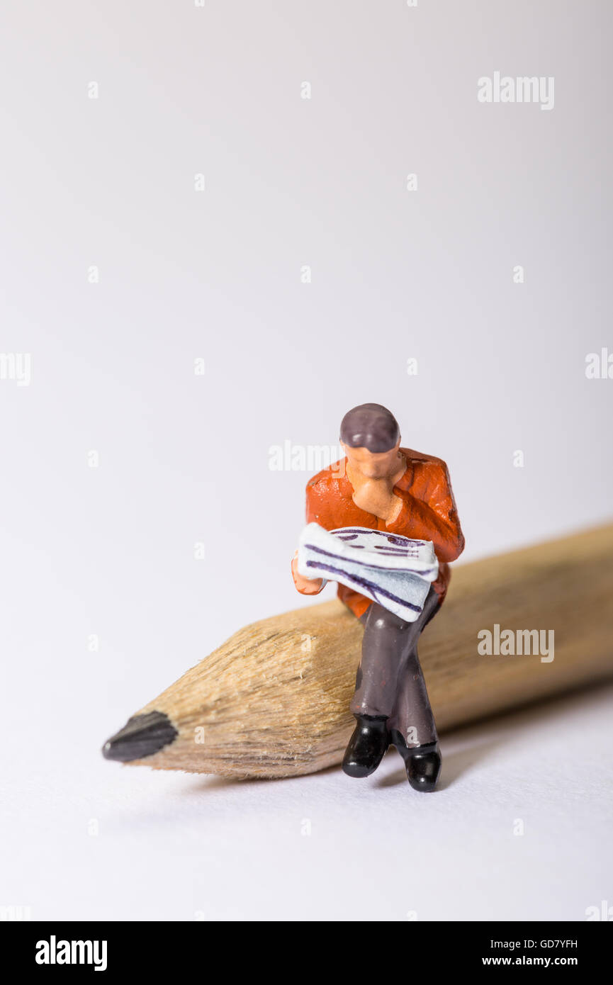 Concept image of a male figure looking through a newspaper sat on a pencil looking at a crossword puzzle or looking - Stock Image