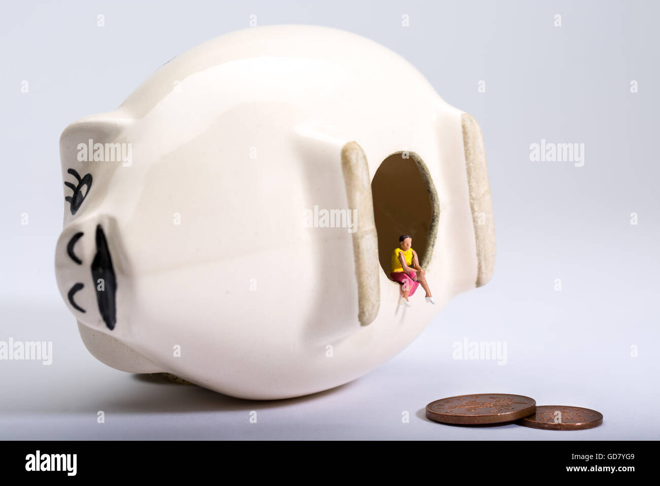 concept image of a lone figure with an empty piggy bank to illustrate low savings and low interest rates on savings - Stock Image