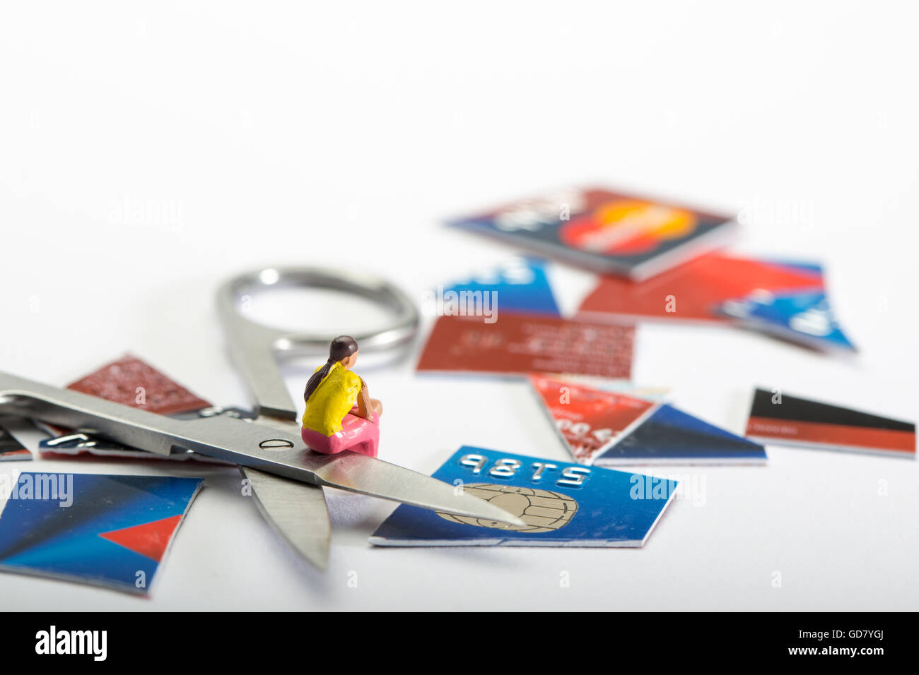 Credit Card dept concept image of a female figure sat with a cut up credit card and a pair of scissors - Stock Image