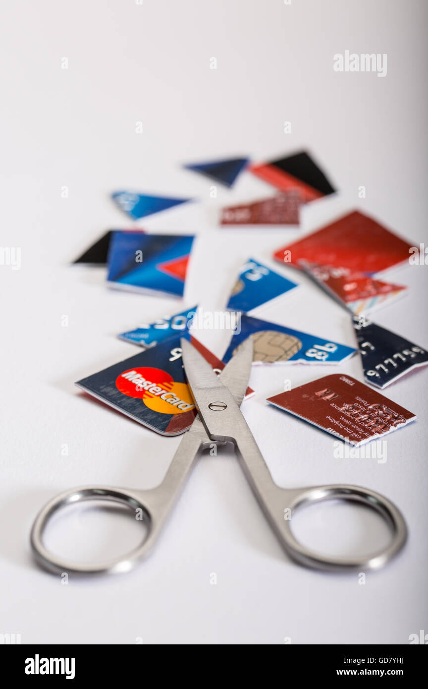 Credit Card dept concept image of a cut up credit card and a pair of scissors - Stock Image