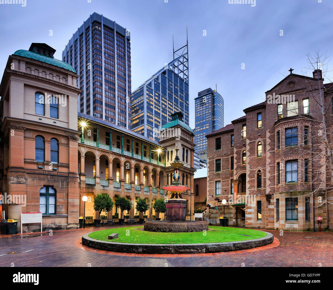 Stone facades of Sydney royal eye hospital wings around decorated fountain agaist modern office skyscraper towers. - Stock Image