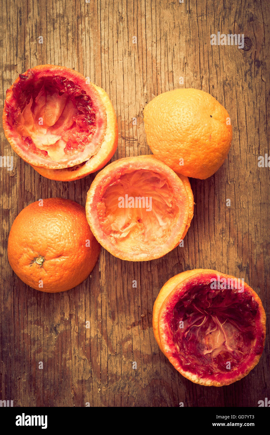 oranges peels scattered on a rustic table - Stock Image
