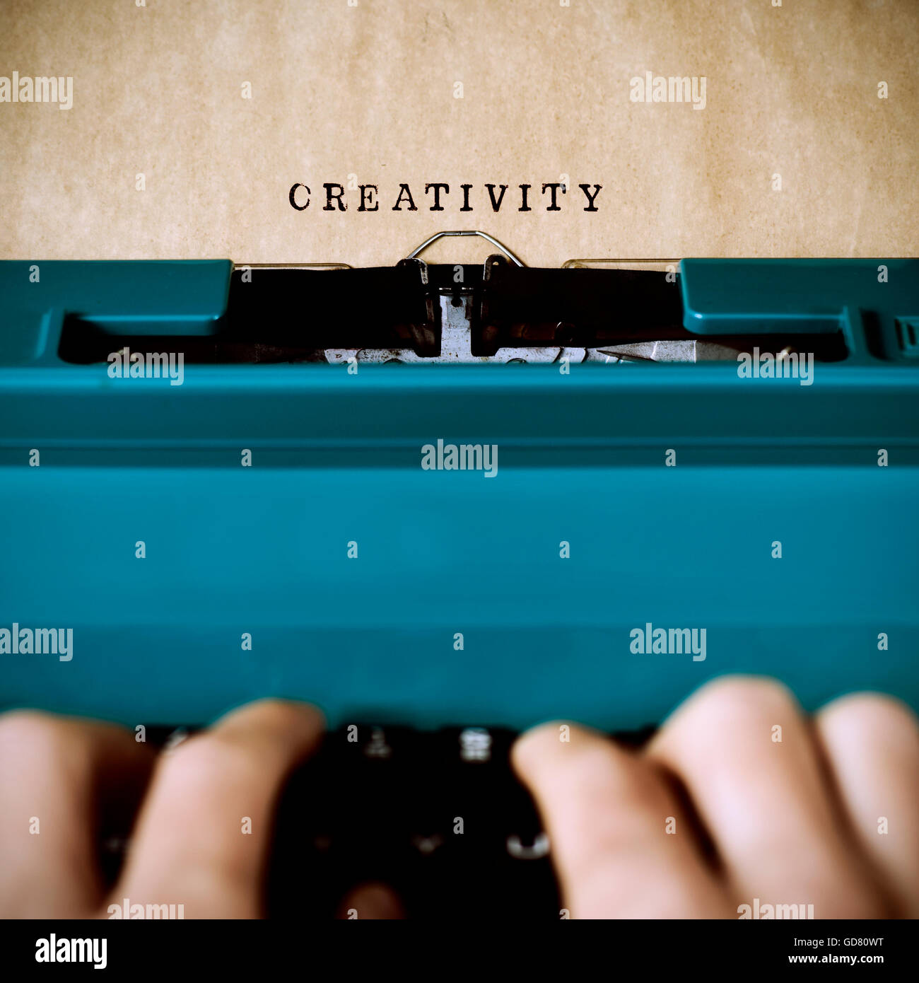 closeup of the hands of a young man typewriting the word creativity in a yellowish foil with an old blue typewriter - Stock Image