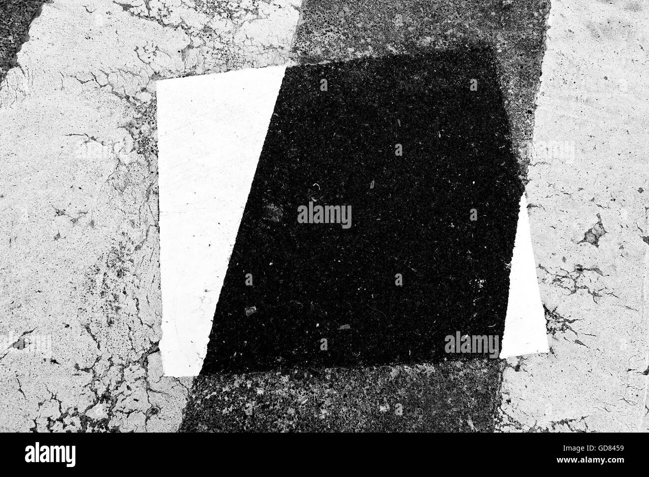 patch on a crosswalk. Black and white - Stock Image
