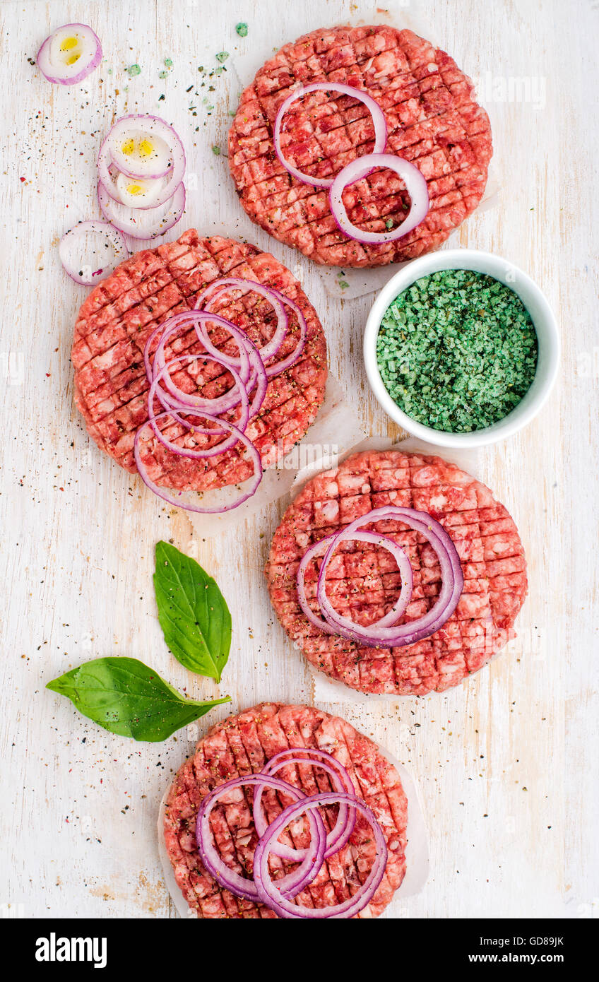 Raw beef meat cutlet for making burgers with onion rings and spices on white wooden background, top view, vertical - Stock Image