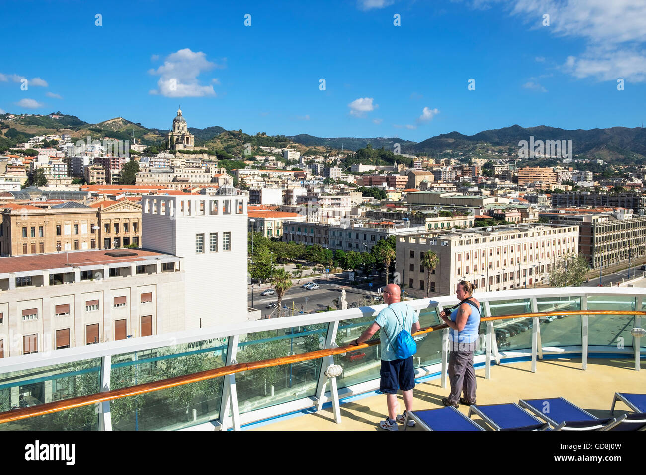 Tourists get their first view of Messina, Sicily, from a cruise ship that has just arrived in the port - Stock Image