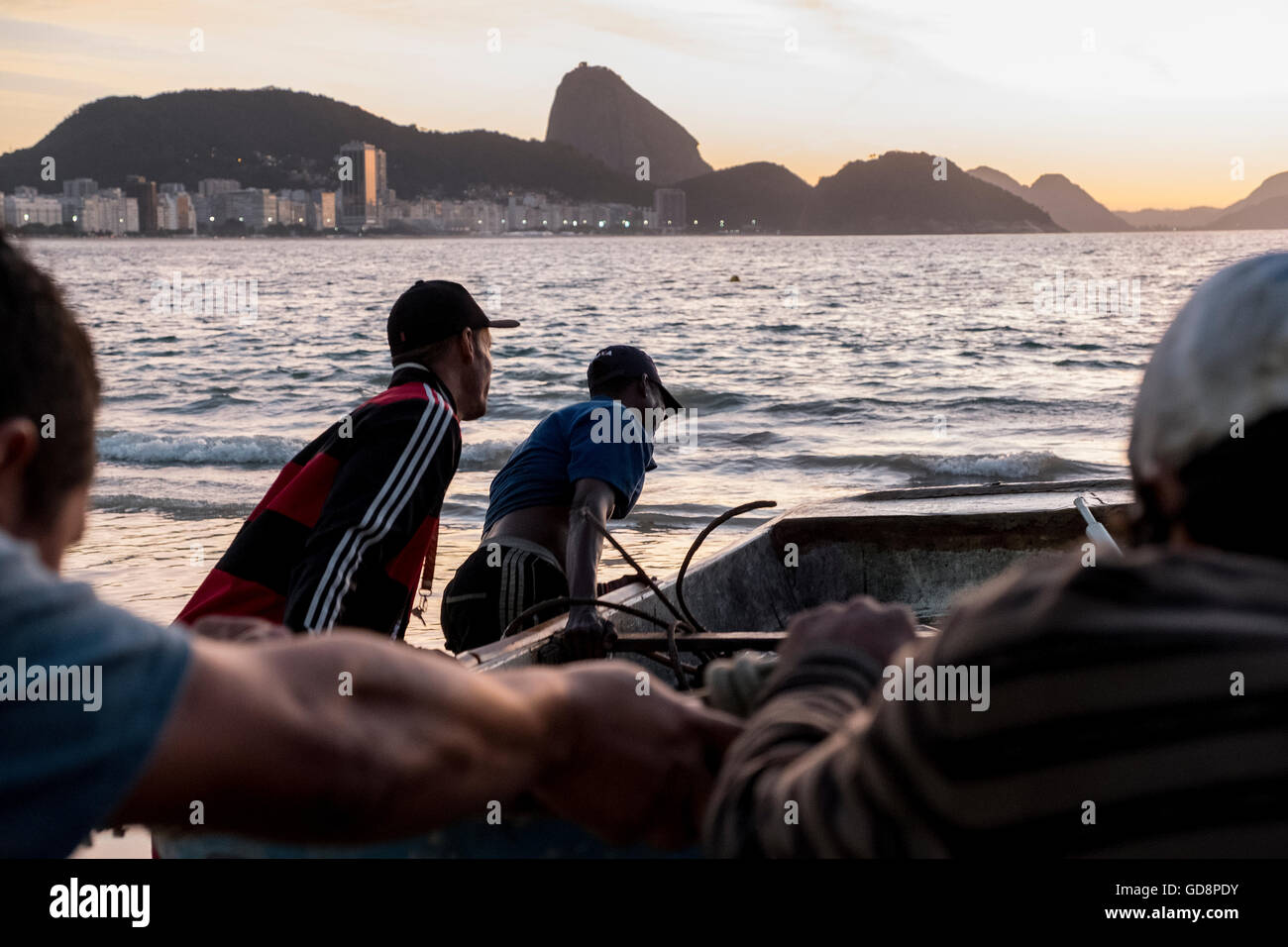 Fishers and helpers of the Copacabana Beach Fisher Association push boats into the sea together near Rio de Janeiro, - Stock Image