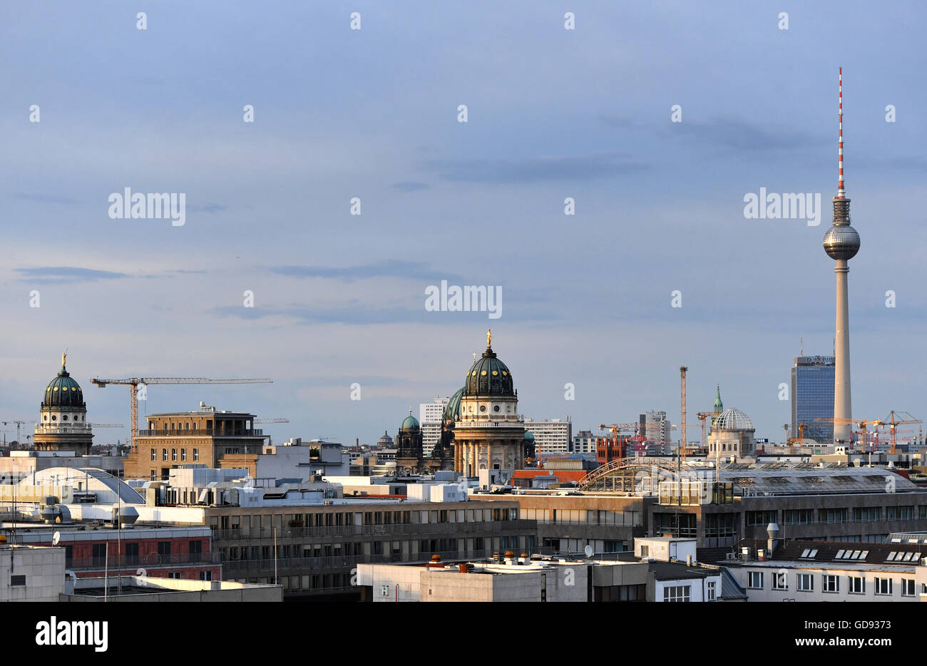 Berlin, Germany. 12th July, 2016. View from the EWerk in Berlin-Mitte across the rooftops of the capital with the French cathedral (l-r), German cathedral (Berlin cathedral behind it), the cupola under construction of the city castle, the hotel Park Inn and the TV Tower on Alexanderplatz in Berlin, Germany, 12 July 2016. Photo: Jens Kalaene/dpa/Alamy Live News Stock Photo