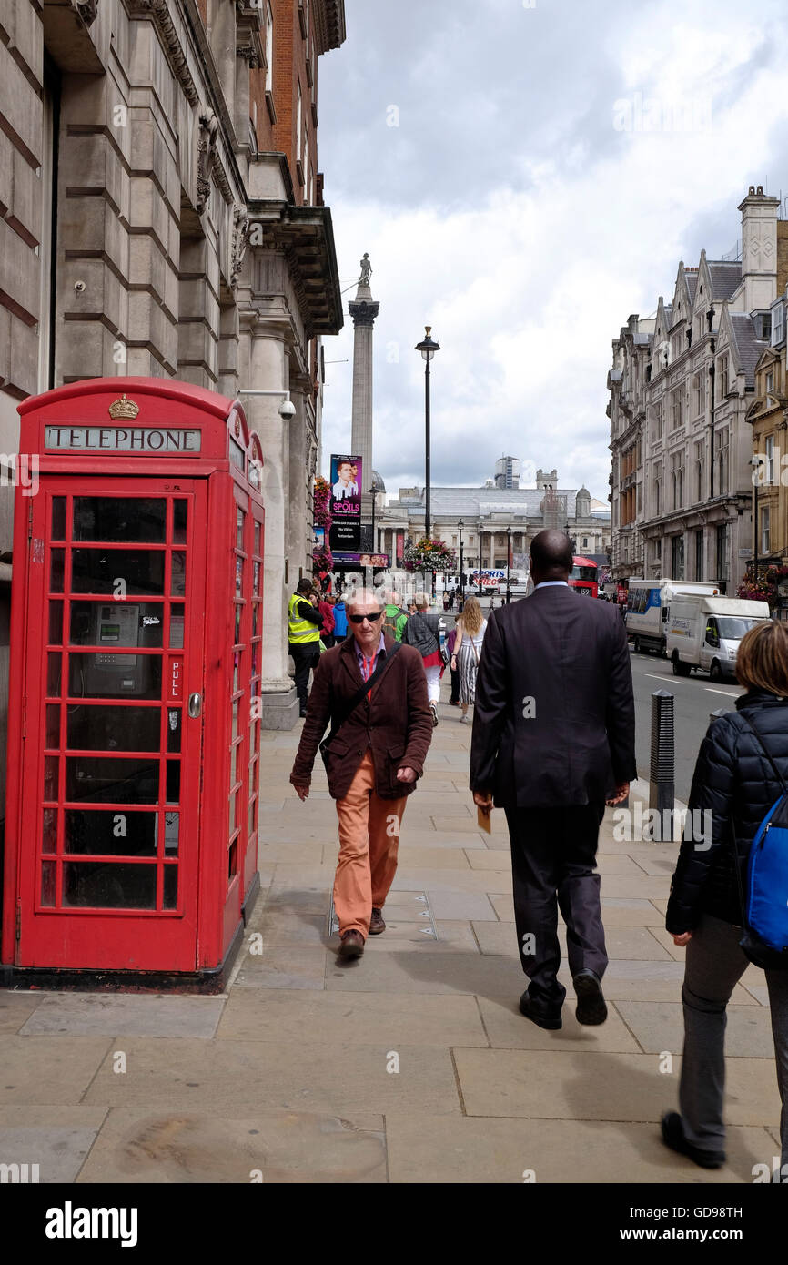 The red K6 telephone box a telephone kiosk for a public telephone in the UK. Nelsons Column a London landmark in - Stock Image