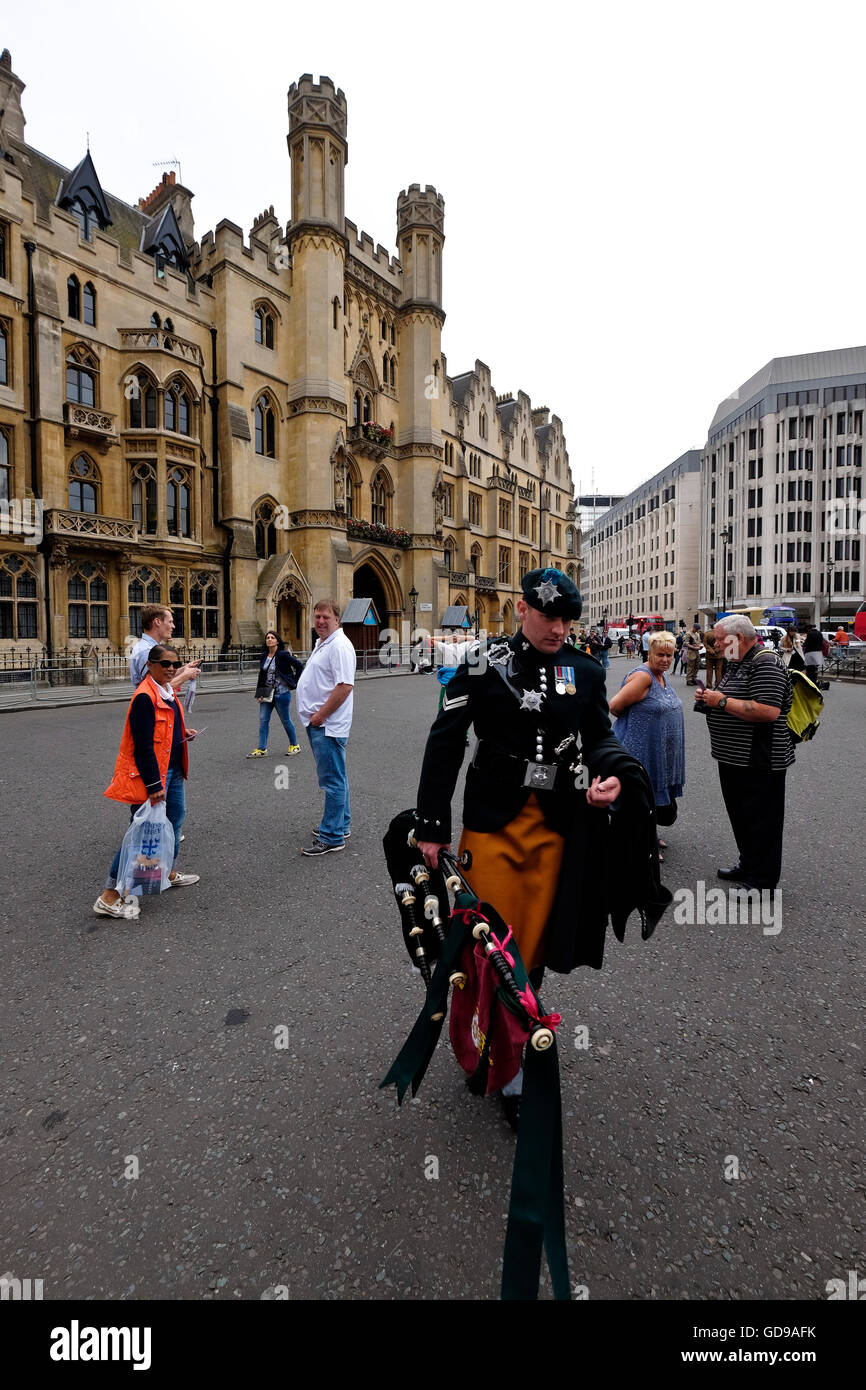 A piper walks towards Westminster Abby a London landmark with Dean's Yard Westminster in the background - Stock Image