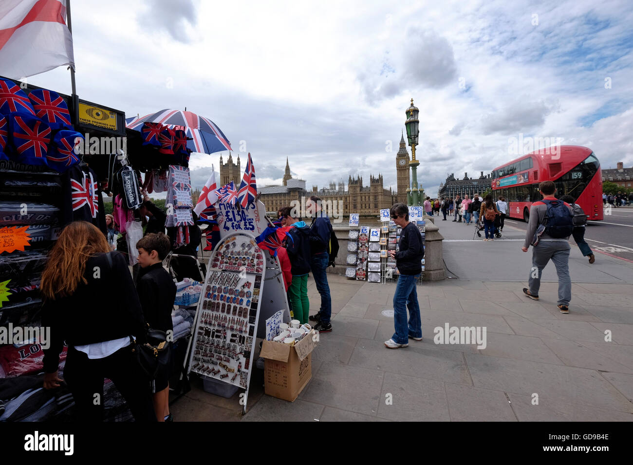 A street vendor selling souvenirs looking over Westminster Bridge with the Houses of Parliament a London landmark - Stock Image