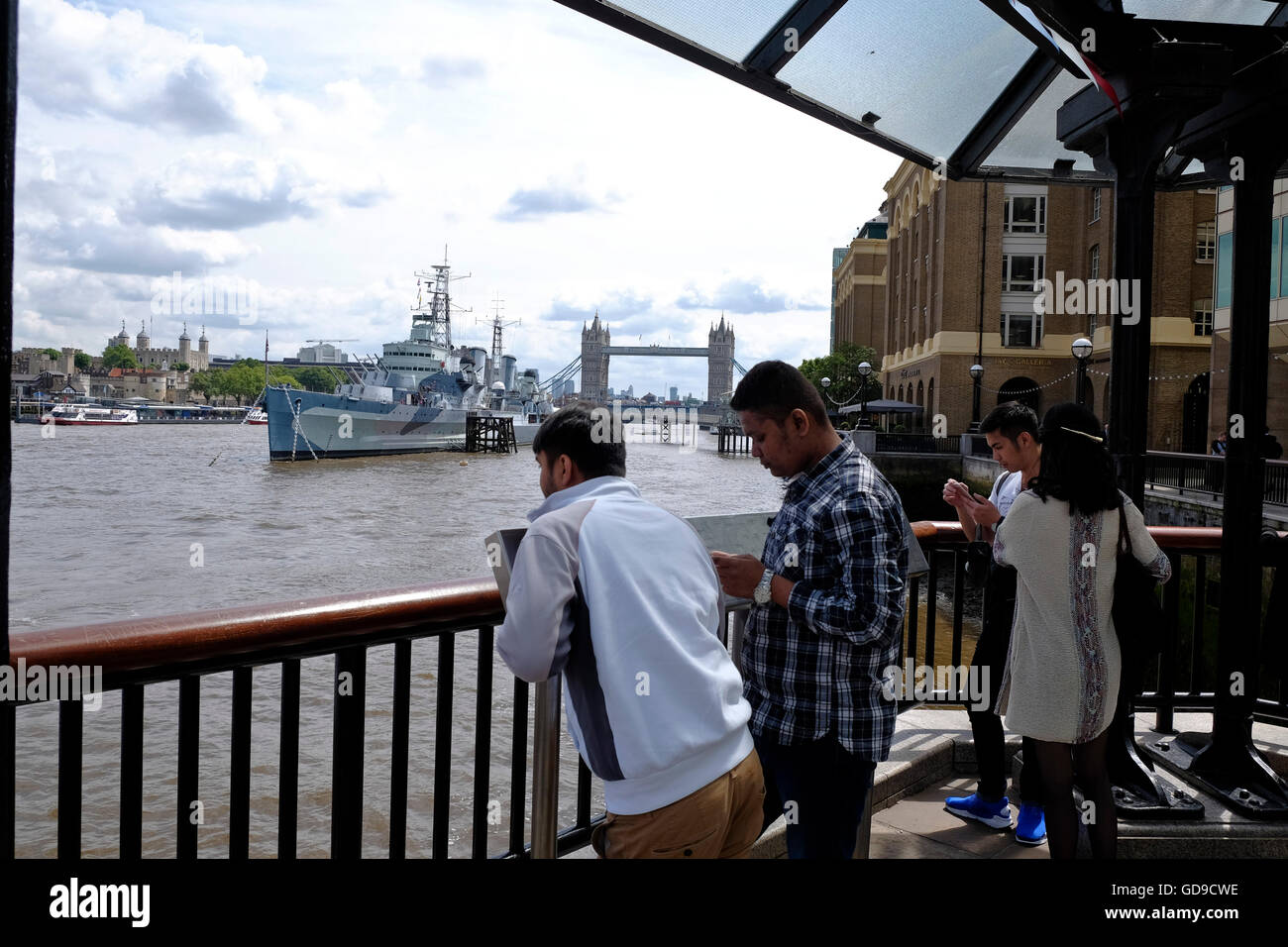 Tourists on the South Bank walkway with HMS Belfast and Tower Bridge a London landmark in the background - Stock Image