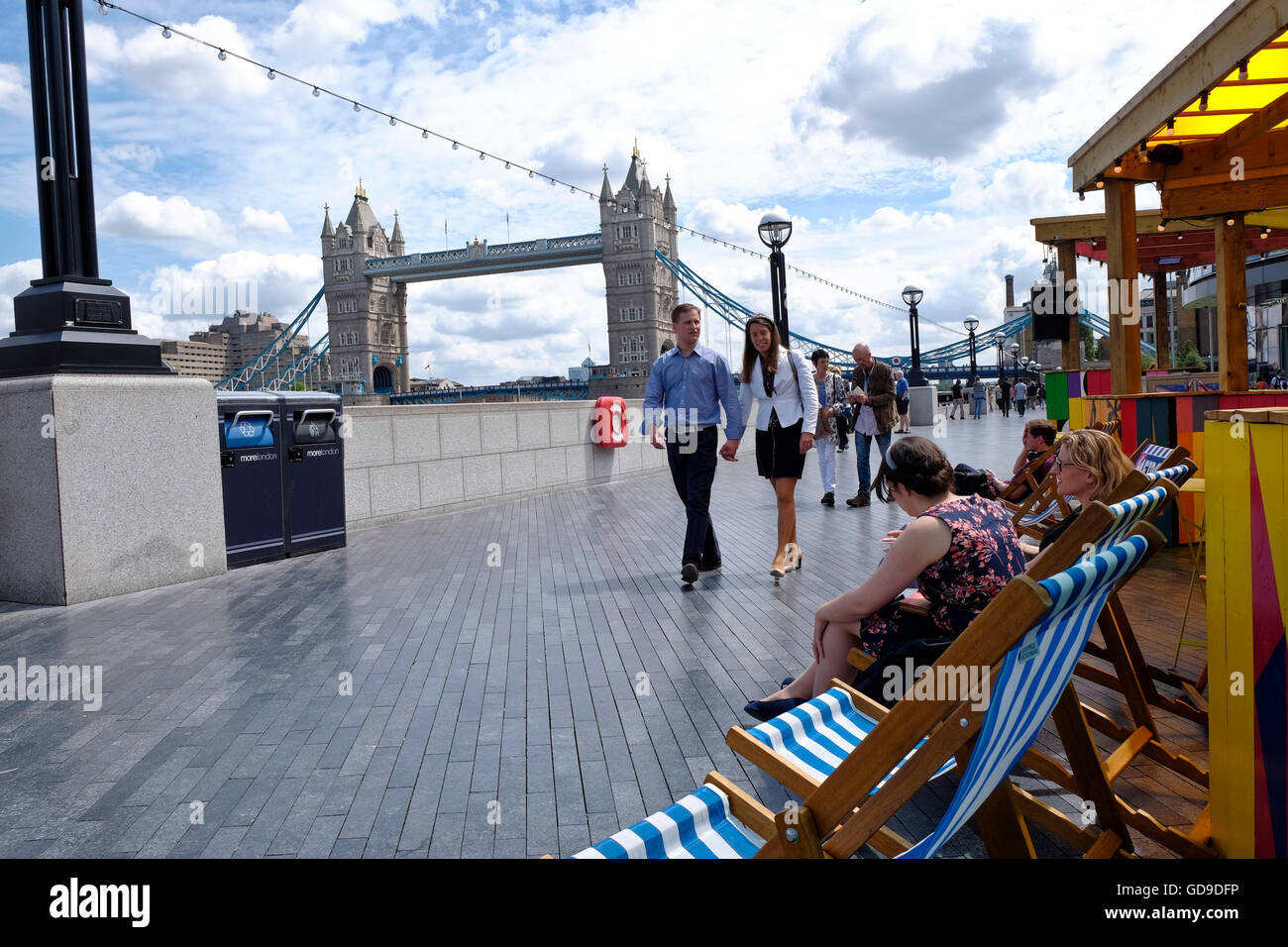 London, United Kingdom. Tourists sit and relax in deck chairs on the walkway on the south bank of the Thames Tower - Stock Image