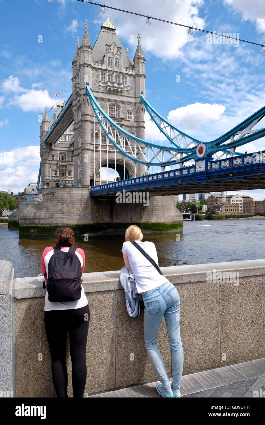 Tourists lean on the embankment wall looking at Tower Bridge a landmark in the City of London - Stock Image