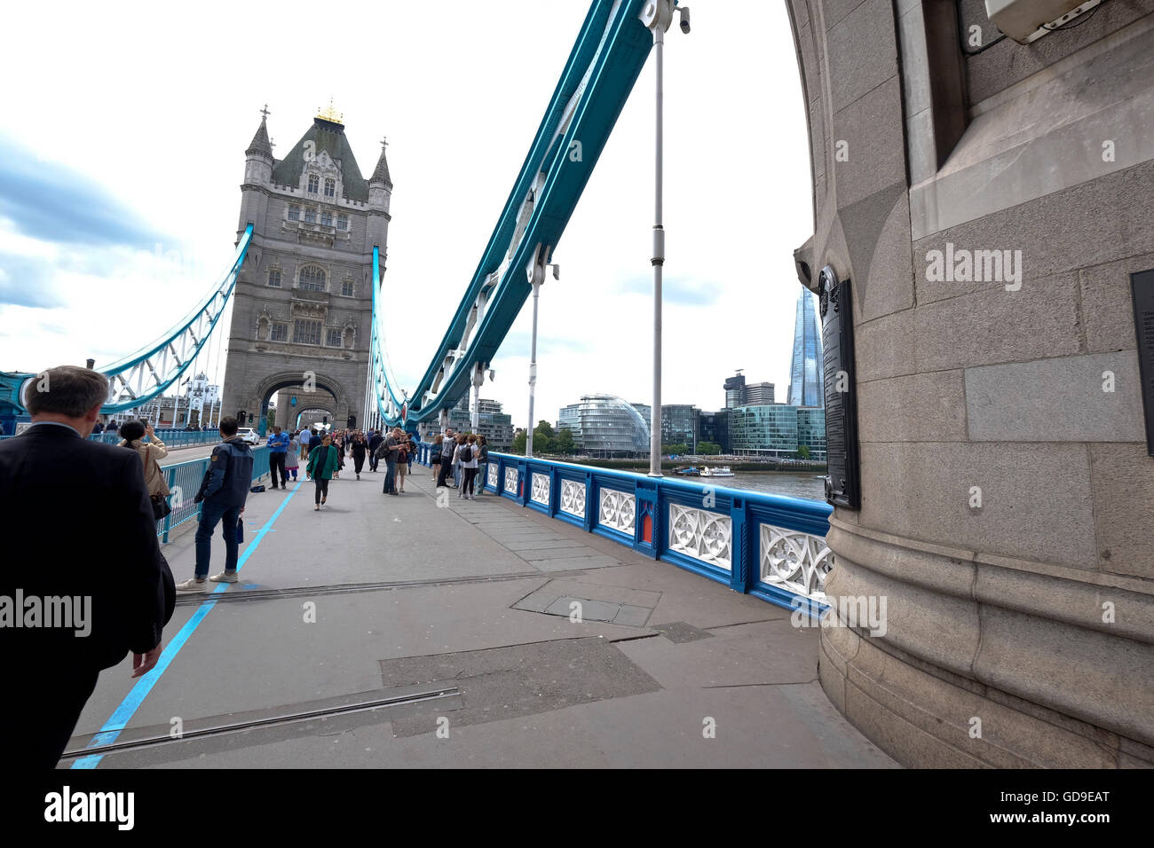 Pedestrians passing under a tower on London Bridge with the other tower in the background - Stock Image