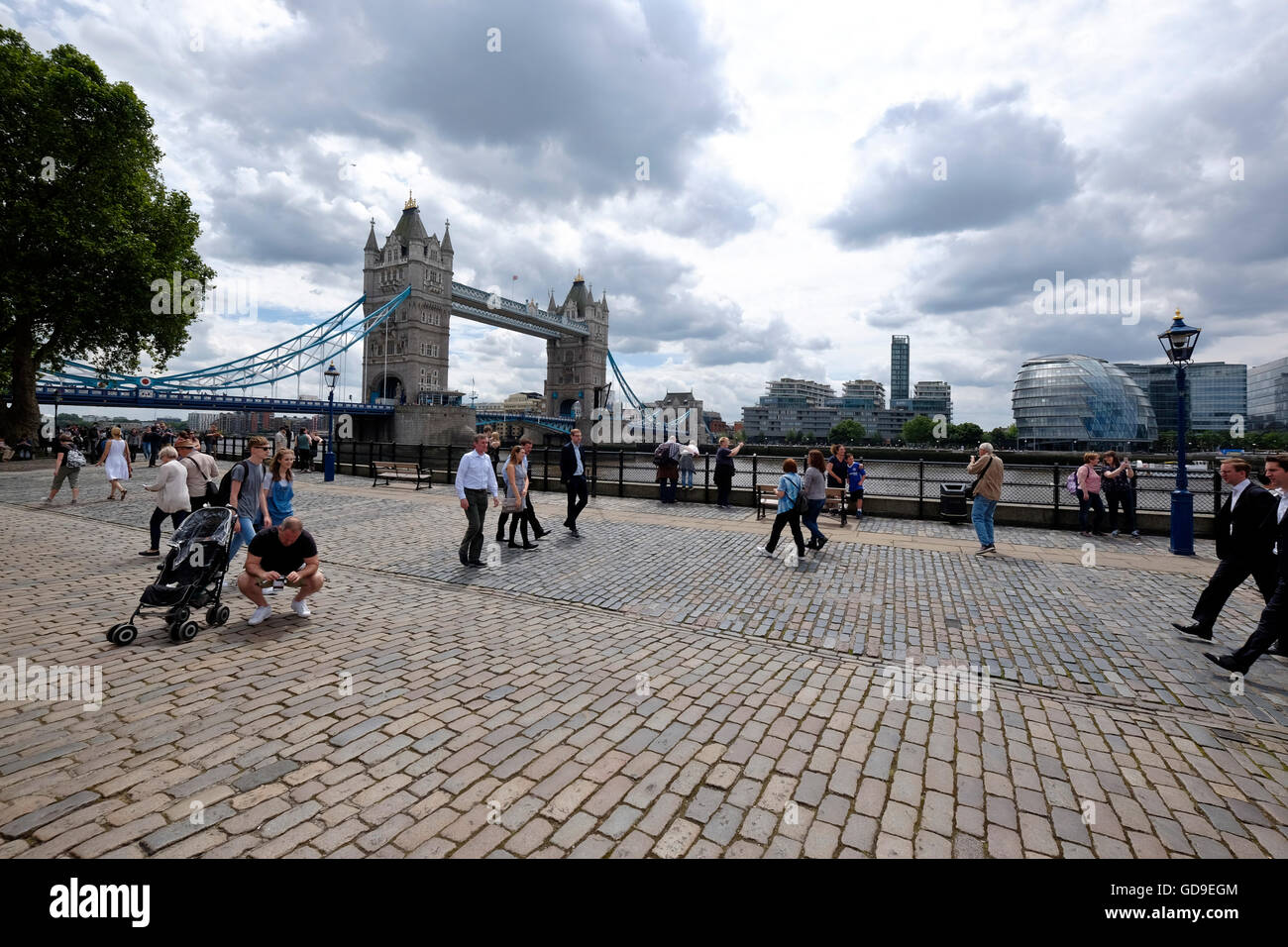 Tourists on Victoria Embankment London with Tower Bridge on the left and City Hall on the right in the background - Stock Image