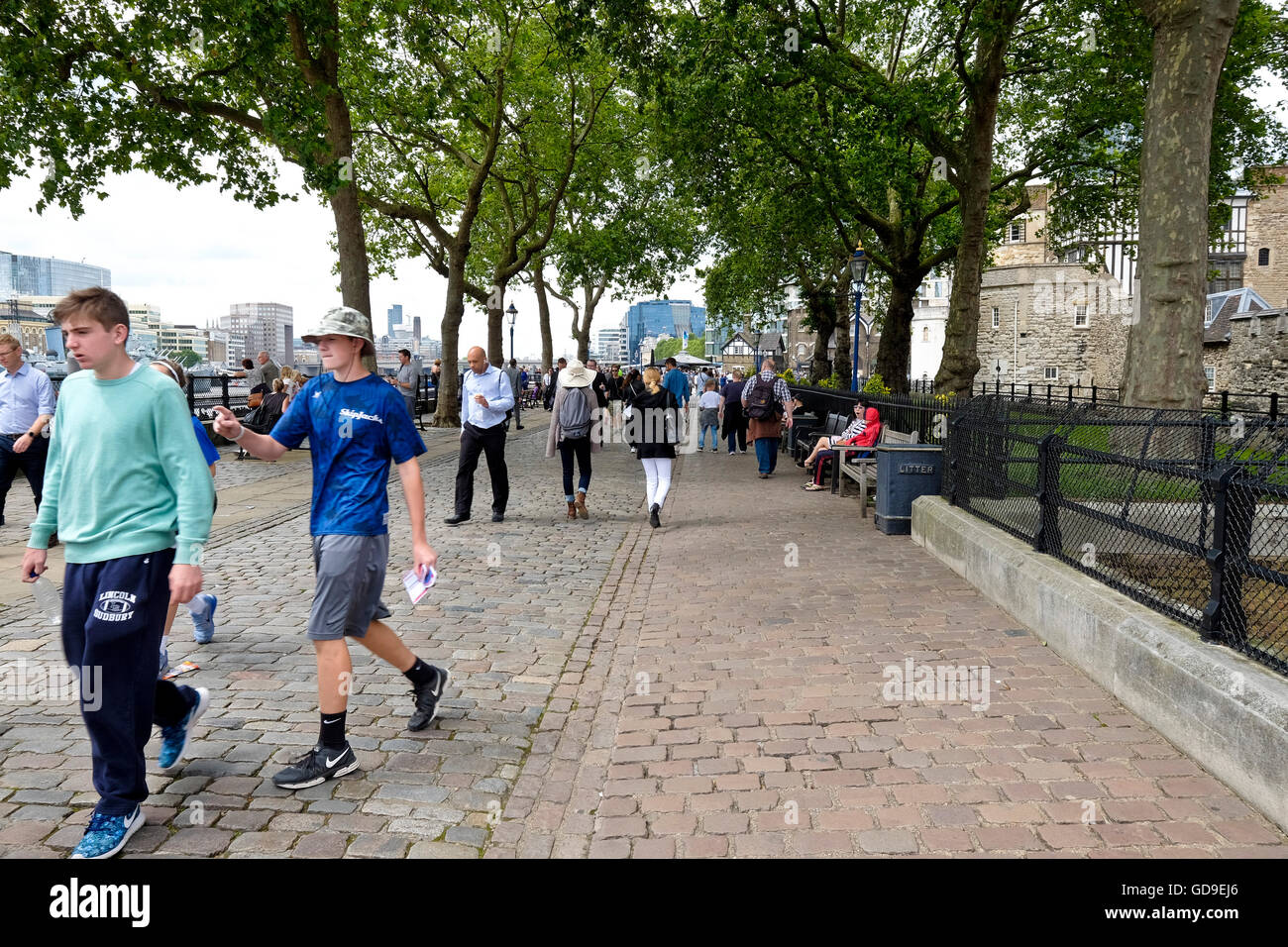 Tourists walk under the trees on Victoria Embankment along the river Thames.. London Tower a London landmark is - Stock Image