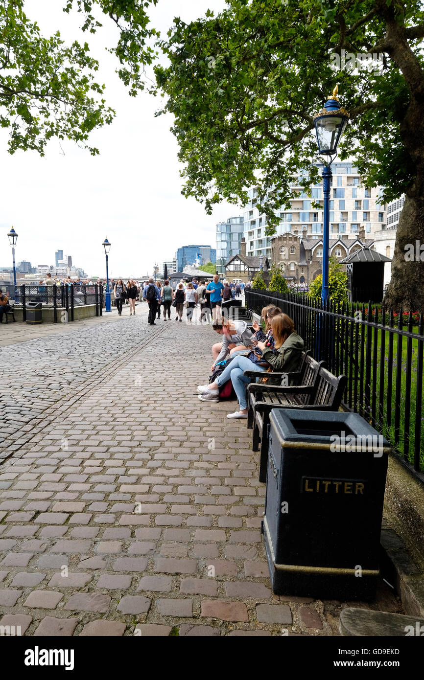 London, United Kingdom. Tourists sit on benches under trees on the Victoria Embankment along the Thames river Tower - Stock Image