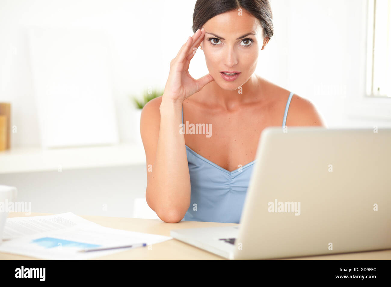 Stylish female in blue blouse feeling tension at work - Stock Image