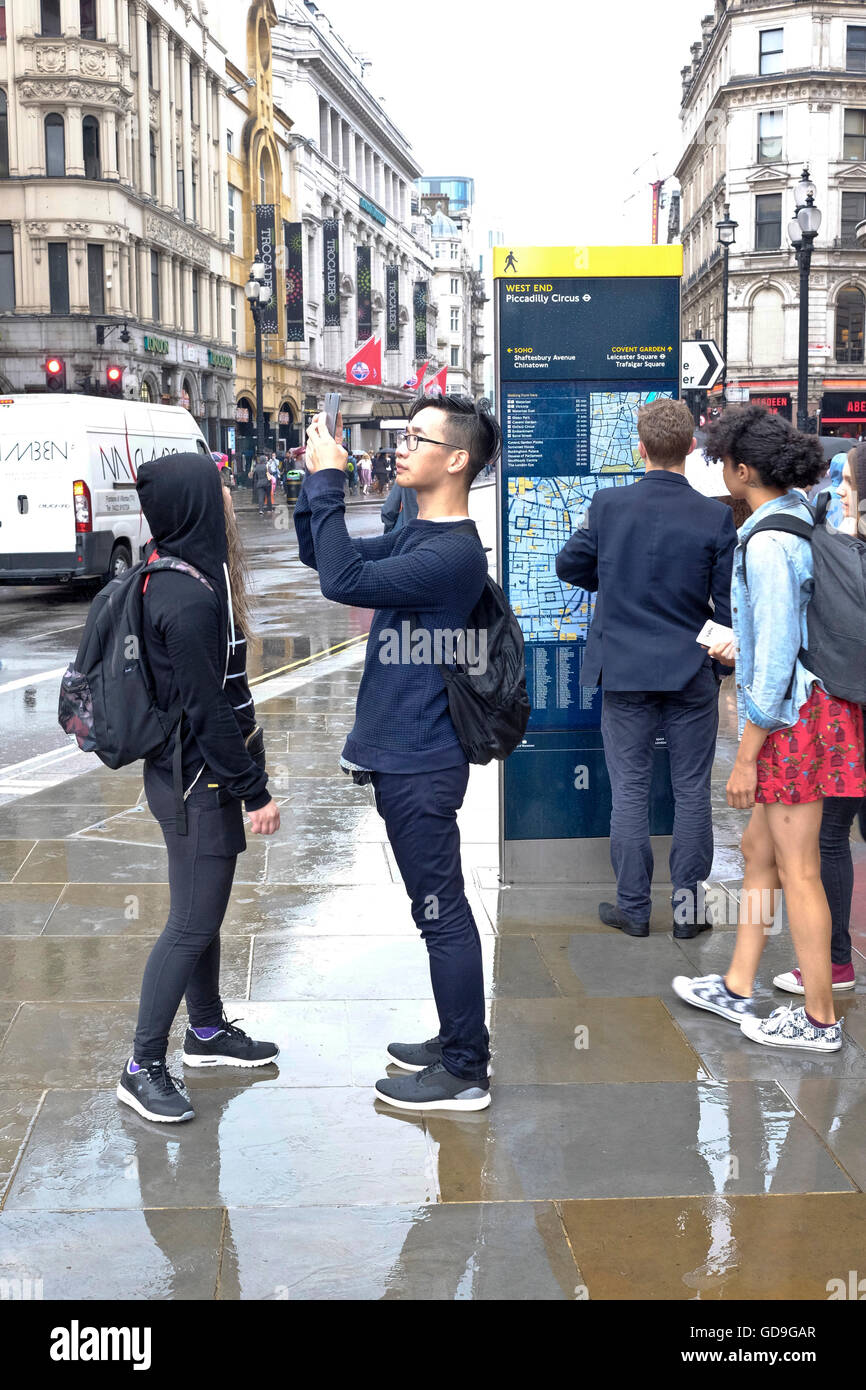 Piccadilly Circus London. A Chinese tourist takes a photograph of Eros with his smart phone on a wet and rainy day - Stock Image