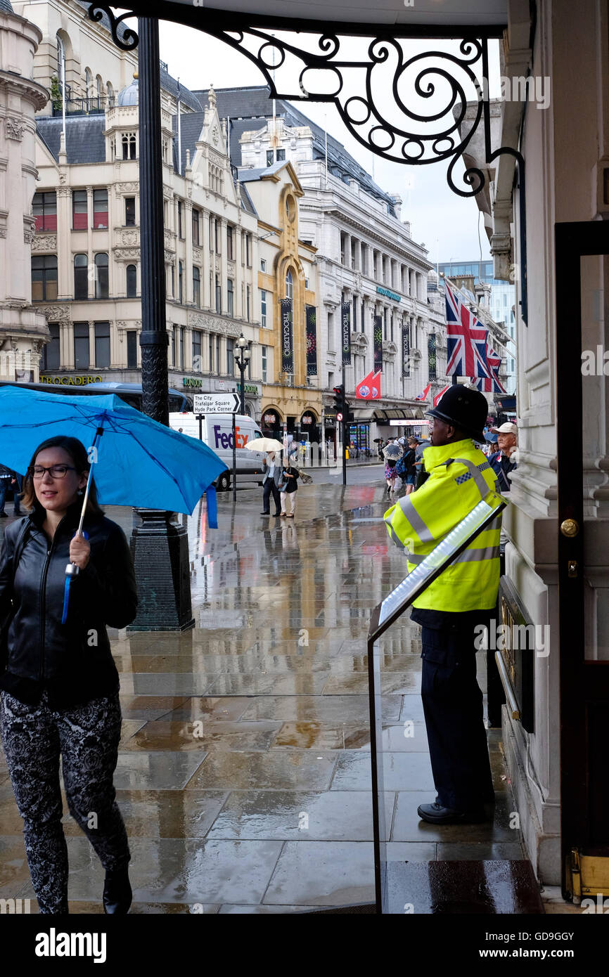 A British policeman on the beat on a rainy day in the City of London - Stock Image