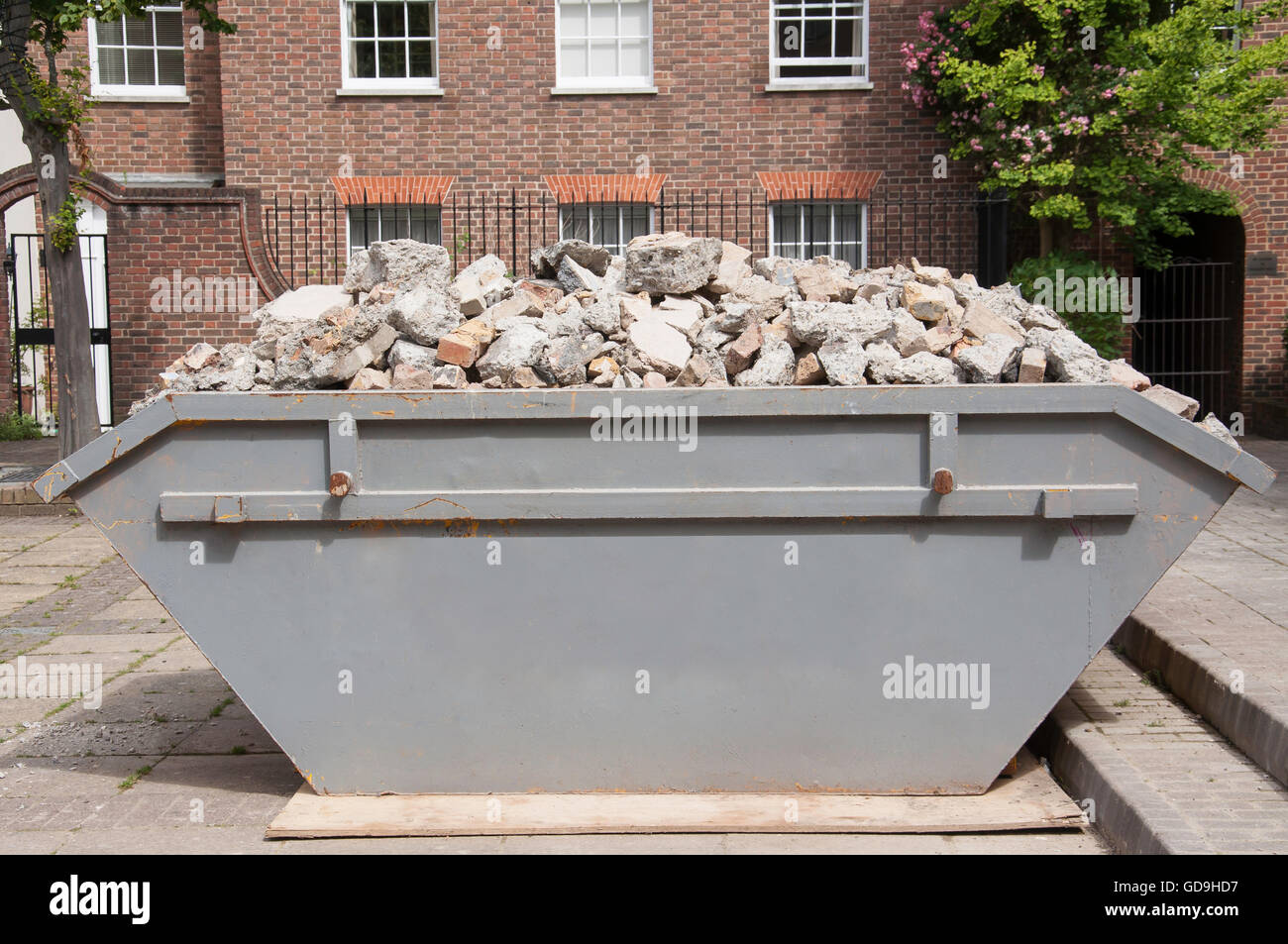 Skip full of aggregate, Lower Square, Isleworth, London Borough of Hounslow, Greater London, England, United Kingdom - Stock Image