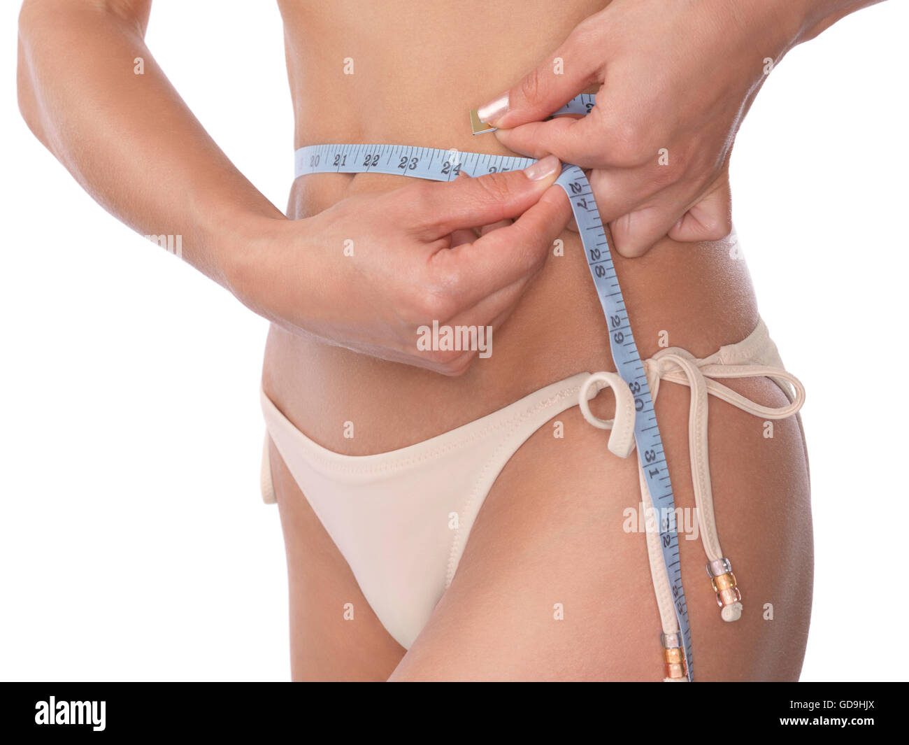 Young slim woman measuring her waist with a tape measure - Stock Image