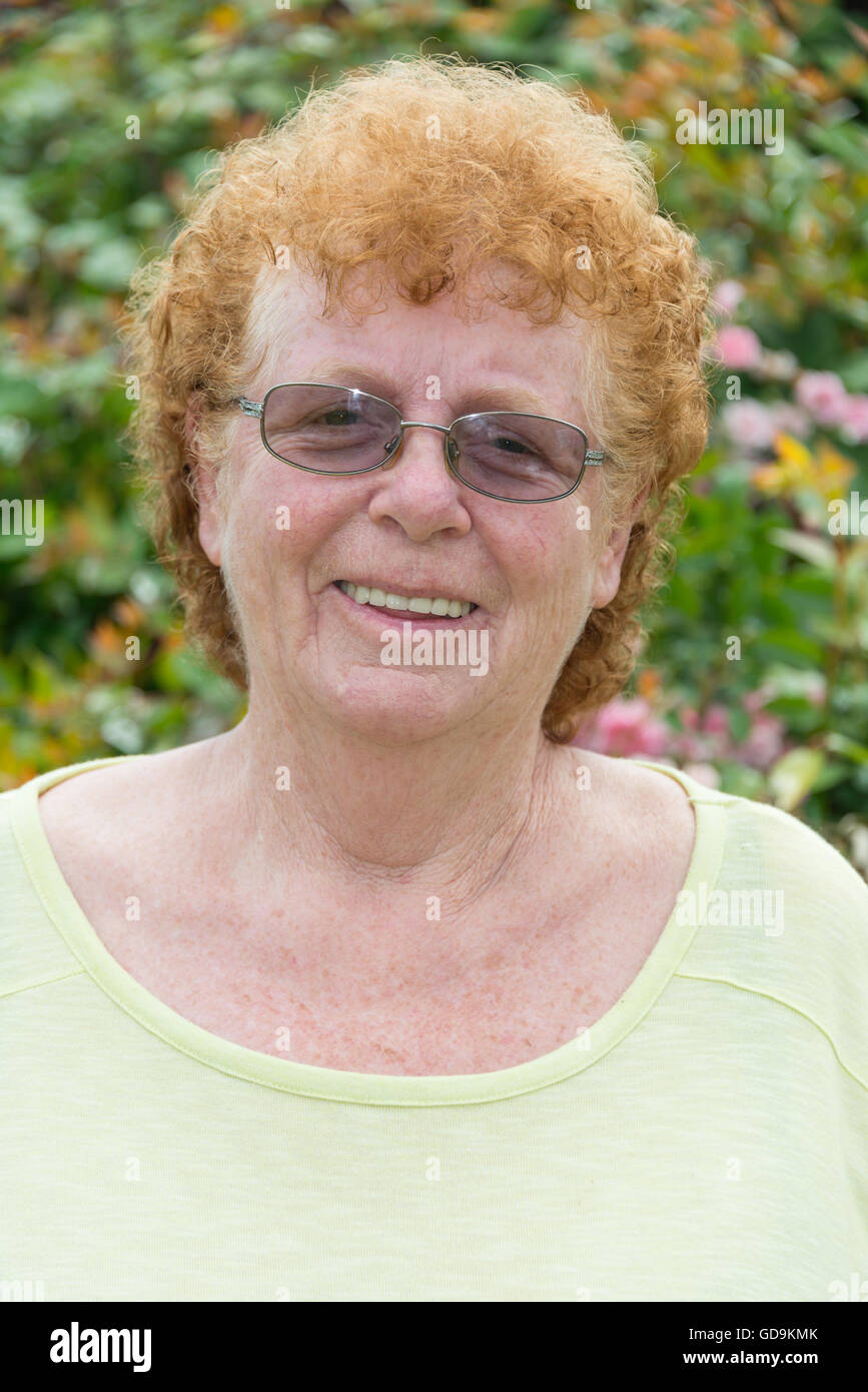 Head and shoulders of red-headed woman (60s), Stanwell Moor, Surrey, England, United Kingdom - Stock Image