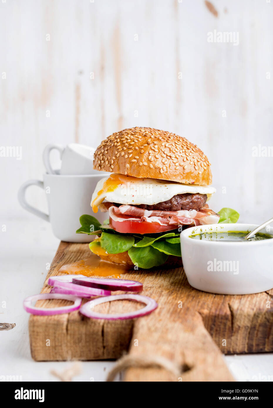 Fresh homemade burger with beef cutlet, egg, prosciutto and vegetables on wooden serving board with onion rings - Stock Image