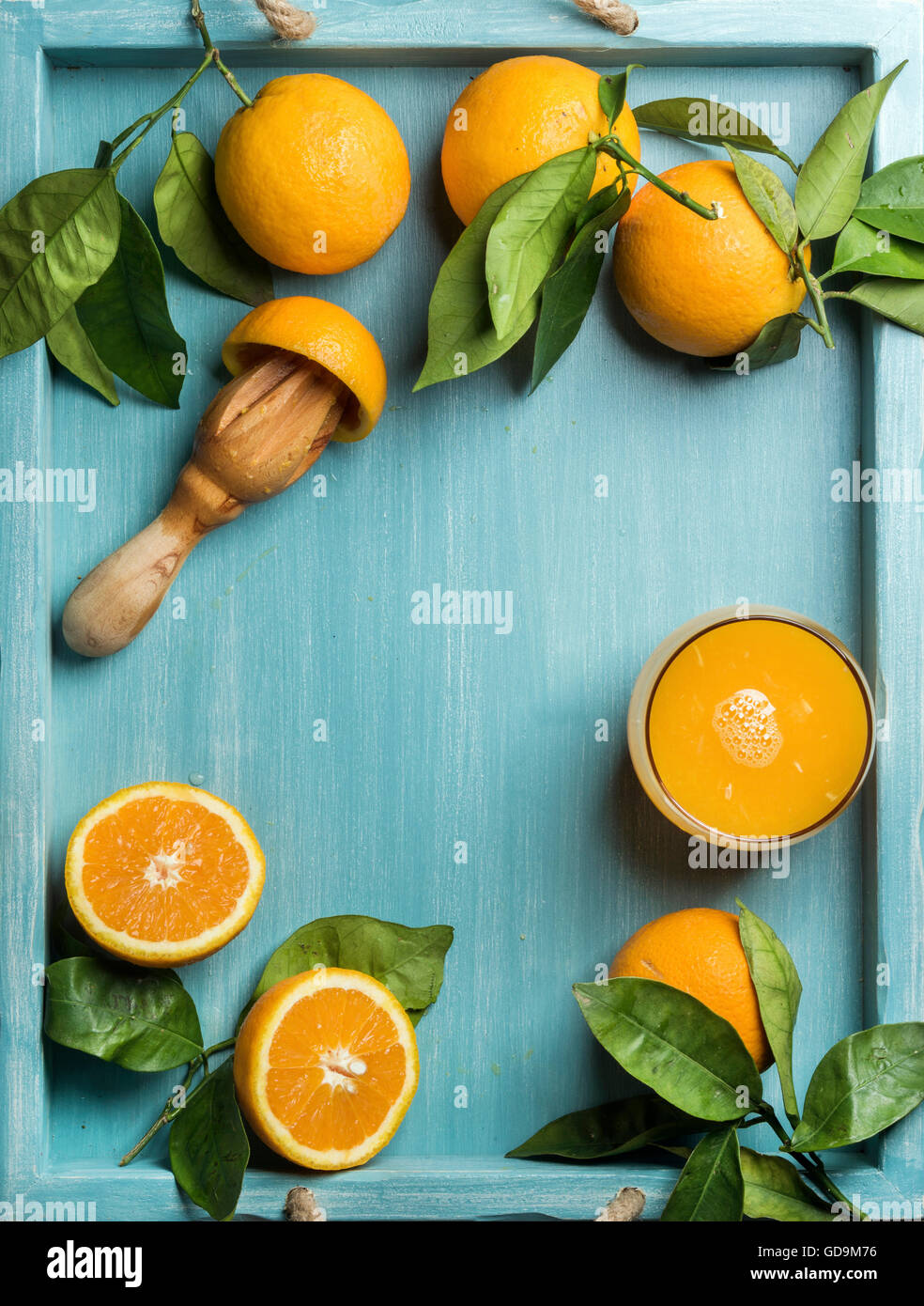 Glass of freshly squeezed orange juice and oranges with leaves on wooden turquoise blue painted background. Top - Stock Image