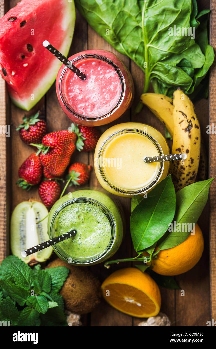 Fresh blended smoothies in glass jars with straws on wooden baclground served with watermelon, kiwi, orange, banana, - Stock Image