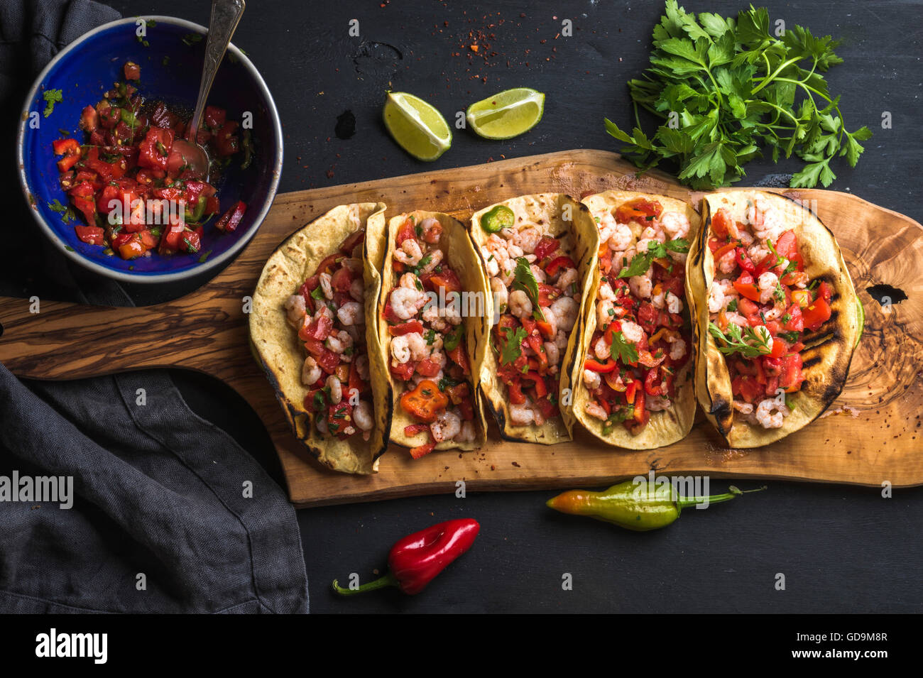 Shrimp tacos with homemade salsa sauce, limes and parsley on wooden board over dark background. Top view. Mexican - Stock Image