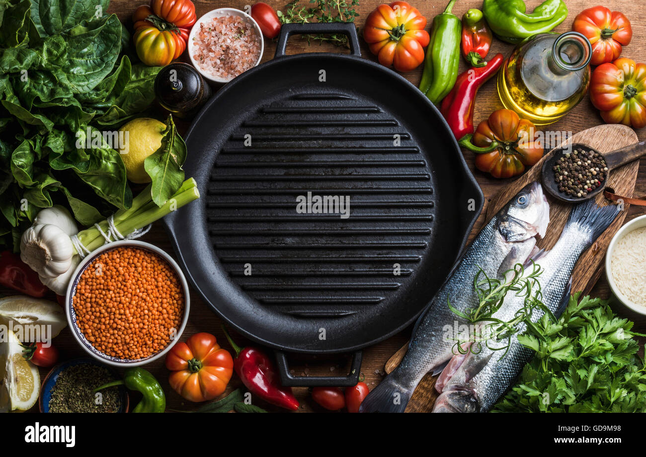 Ingredients for cooking healthy dinner. Raw uncooked seabass fish with vegetables, grains, rice, herbs and spices - Stock Image