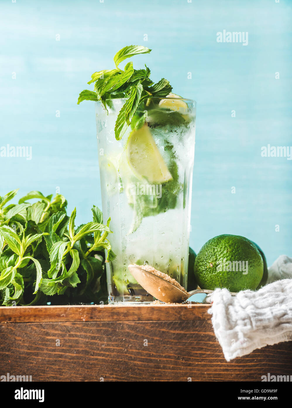 Homemade Mojito cocktail in tall glass served with bunch of mint, brown sugar and limes on wooden board. Turquoise - Stock Image